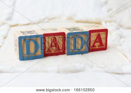 Wooden Alphabet Blocks On Quilt Spelling Dada