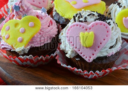 Valentine love muffins colorful cupcakes decorated with marzipan hearts served on wooden round saucer over red table cloth close up view