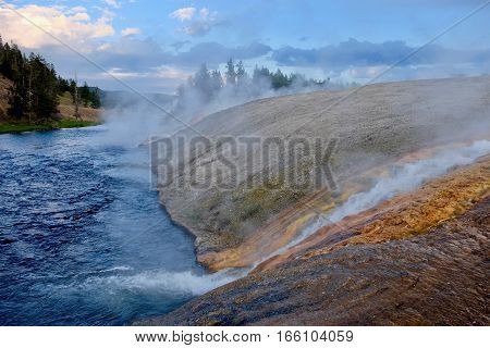 Yellowstone. Grand Prismatic Spring. Hot water from the Midway Geyser Basin cascades into the Firehole River in Yellowstone National Park. Wyoming. United States.