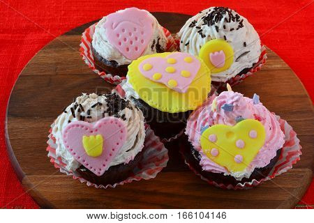 Love muffins colorful cupcakes decorated with marzipan hearts served on wooden round saucer over red table cloth side view
