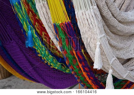 Close up photo of a selection of colorful woven hammocks, taken at the Farmers Market in New Orleans