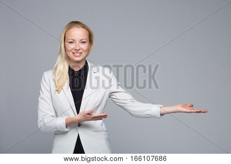 Young businesswoman smiling, holding open palm with empty copy space. Business woman showing hand sign to side, concept of advertisement product. Grey background.