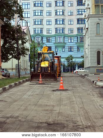 Roadworks in a city with using construction equipment