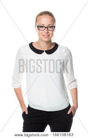 Portrait of beautiful smart young businesswoman wearin black eyeglasses, standing with arms in pockets against white background.