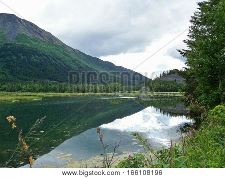 Beautiful summer landscape in Alaska with mountains and clouds reflecting on the water. Relaxing day at the lake or pond with hills and sky mirrored on the surface.