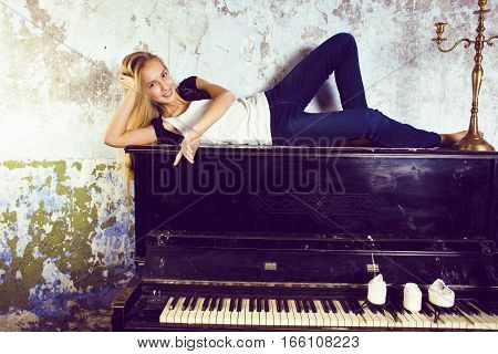 pretty young blond real teenage girl at piano in old-style rusted interior, vintage concept