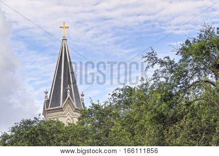 A cross gleams in the sunlight atop a tall steeple on a church in the southern United States.