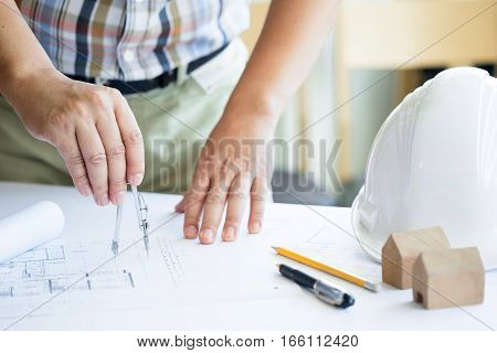 Close-up Of Person's Hand Drawing Plan On Blue Print with architect equipment