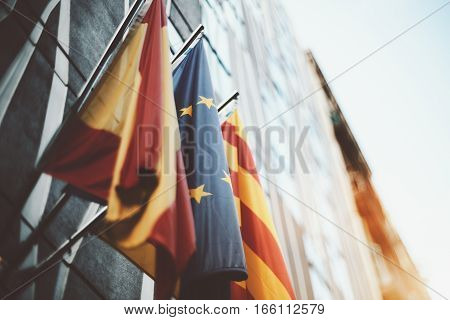 True tilt shift shooting of waving flags on modern business office facade in Barcelona: European Union Catalonia Spain sunny summer day with clean blue sky