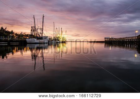 Sunset over Shem Creek in Mount Pleasant, South Carolina with the fishing boats in the distance.