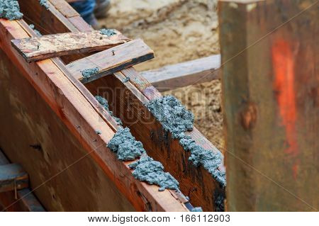 Closeup of foundation excavation with fresh poured concrete and embedded steel reinforcement bars to form continuous footing