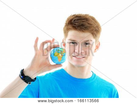 happy student in blue t-shirt holds in his hand a small globe.the photo has a empty space for your text