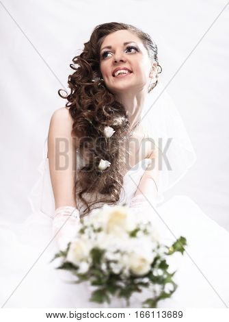 portrait of bride with bouquet on light background