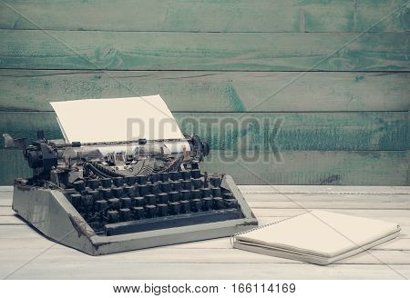 Dirty vintage tapewrite with blank notebook on the wooden table