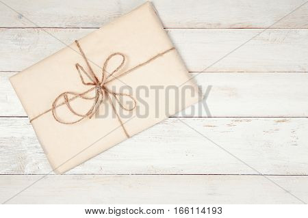 Wrapped gift box on white wooden table with copy space