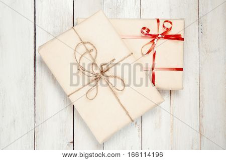 Two wrapped gift boxes on white wooden table
