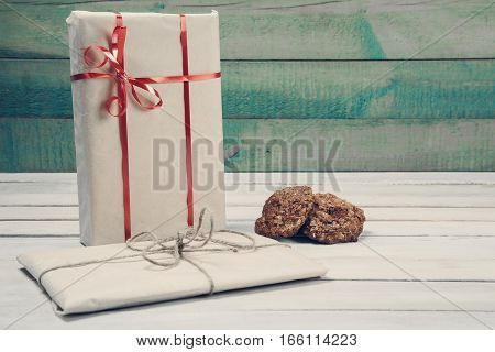 Two wrapped gift boxes and home made cookies on wooden table