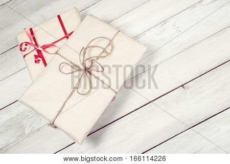 Two gift boxes on white wooden table with copy space