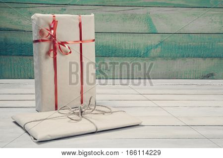 Two wrapped gift boxes on wooden table with copy space