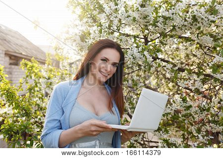 Young attractive sweet girl with a laptop in the park. Spring mood.