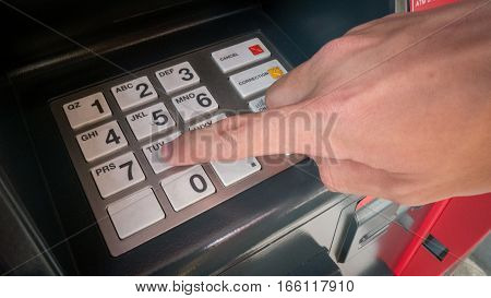 Close Up Of Hand Entering Pin Code At Old Automated Teller Machine (cash Machine).