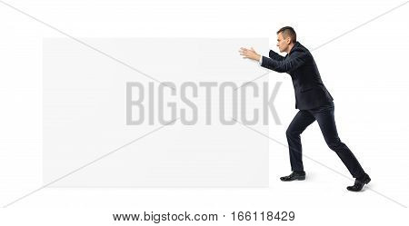 Young businessman is pushing away a big blank banner on white background. Advertising. Business management. Making money