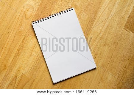 White note book place on wooden table background