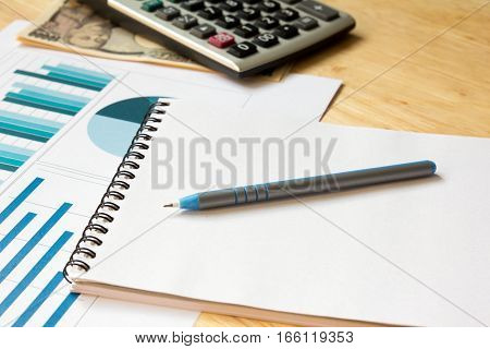 Note book with calculator financial graph pen japanese yen on wooden table background