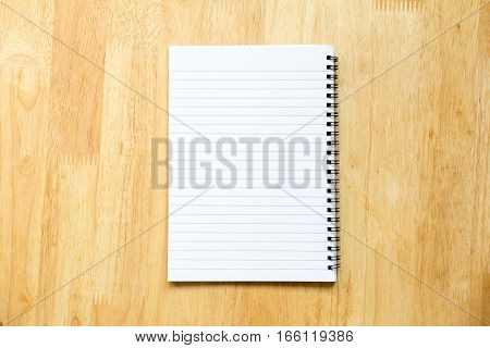 Blank paper note book on wood table background