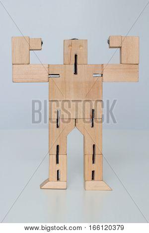 Wooden Robot Toy at athlete pose on white