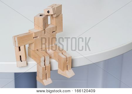 Wooden Robot Toy Sitting and Searching at white