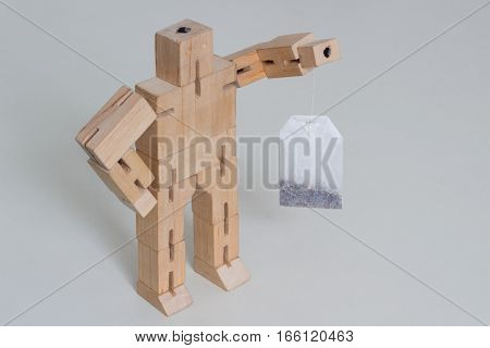 Wooden Robot Toy stand with tea bag at white