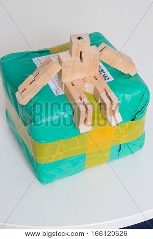 Wooden robot toy sitting on international parcel