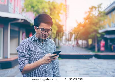 Young Asian Handsome Businessman Concentrated While Reading His Smartphone