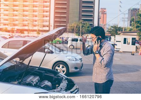 Young Asian Handsome Man Standing By The Broken Down Car