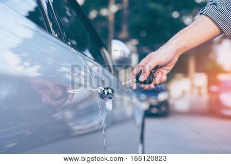 poster of Men's hand using key unlock doors car