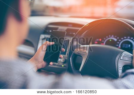 Man using smartphone while driving the car (selective focus) - transportation and vehicle concept