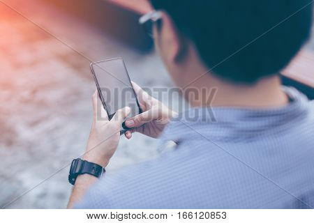 Young asian handsome businessman concentrated while reading his smartphone. Portrait of asian business man reading message with smart phone in outdoor.