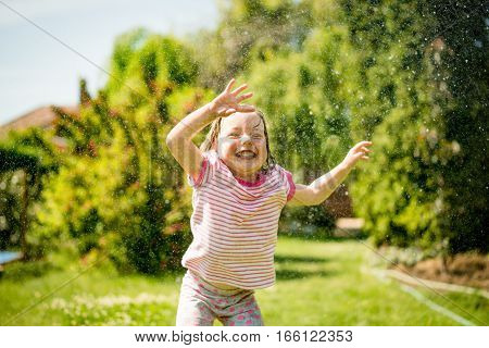 Child refreshing wfrom sprinkling water hose in hot summer day