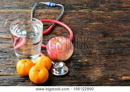 Tools doctor a stethoscope behind an apple, oranges and water glass for healthy put on wood table