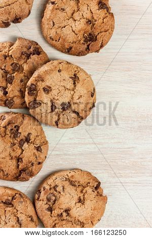 A pile of chocolate chips cookies on a wooden board texture with plenty of copyspace, shot from above