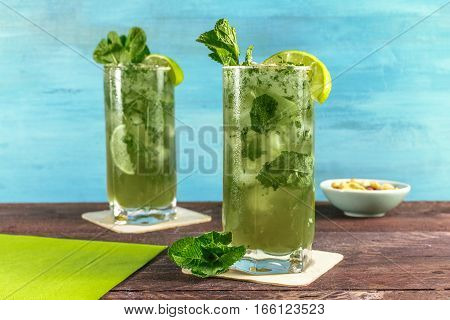 A photo of mojito cocktails with mint leaves, wedges of lime, and a snack, on a vibrant teal wooden background with copy space. Selective focus