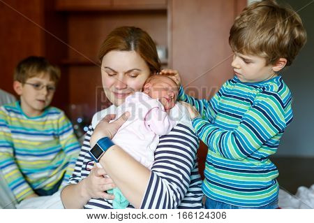 Mother holding newborn baby girl on arm. Two kids boys sitting by mum and sister. Siblings, love. Family on bed in hospital. New born child sleeping. Kids bonding. Mama of three children.