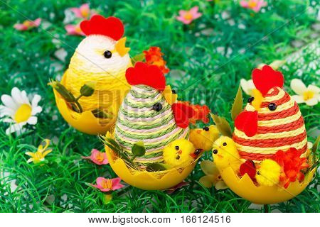 Easter setting with hens chickens and eggs on grass nest.
