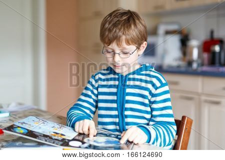 Adorable little kid boy with glasses reading book. Cute happy school child and student learning letters and read. Funny boy making preschool homework. Education concept.