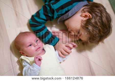 Happy little kid boy with newborn baby girl, cute sister. Siblings. Brother and baby playing together. Kids bonding. Family of two bonding, love.