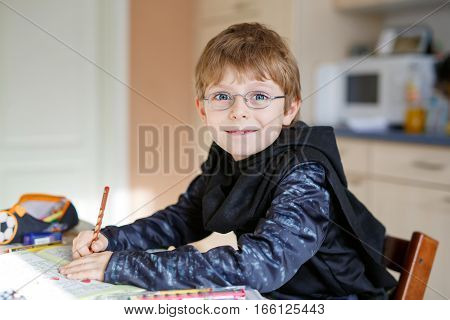 Portrait of cute happy school kid boy with glasses at home making homework. Little child writing with colorful pencils, indoors. Elementary school and education. Kid learning letters and numbers.