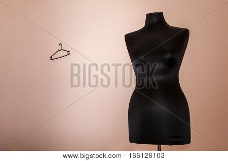 Black sewing mannequin standing on a beige background