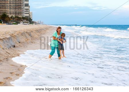 Happy little kid boy and mother having fun on the beach of ocean and on stormy day. Family, mum and cute son playing and making vacations and enjoying summer in Florida, Miami