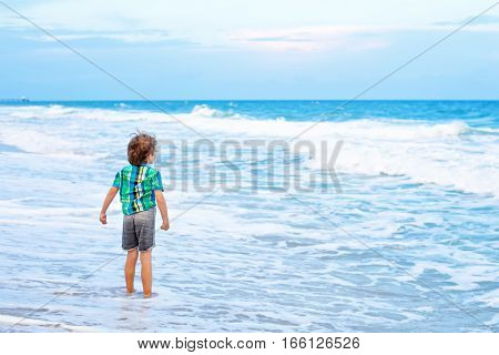 Portrait of happy little kid boy on the beach of ocean looking on dusk, sunset and horizon. Funny cute child making vacations and enjoying summer in Miami, Florida